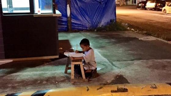 Il bambino studia alla luce del lampione, foto simbolo della lotta per un sogno