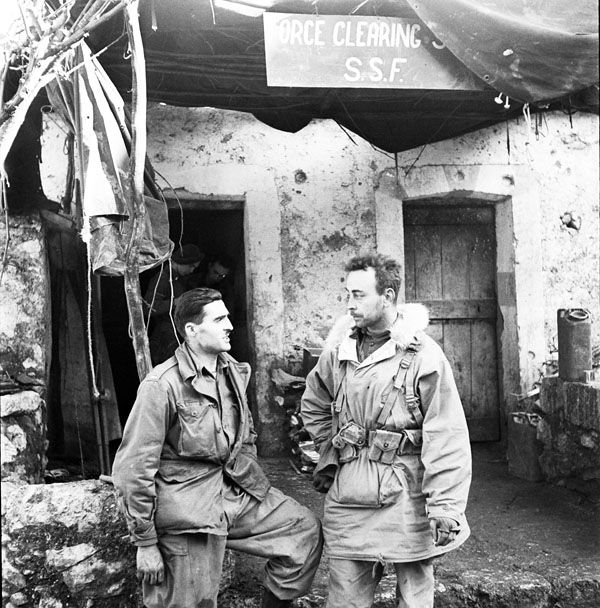 Canadians and Americans wear the same uniform in the First Special Service Force. Lieut. J. Kostelec (Calgary, AB) and Lieut. H.C. Wilson (Olympia, WA) resting on the steps of the Force's Clearing Station, near Venafro, Italy, January 1944.