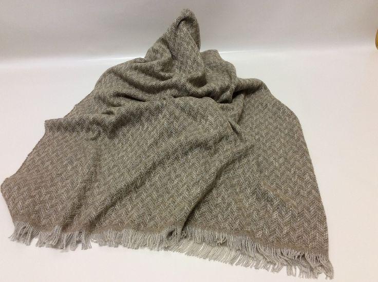 Caldo plaid realizzato nelle fibre naturali di lana e cotone, adatto per riscaldare sia le fredde giornate invernali come pure nelle mezze stagioni. Elegante come oggetto d'arredo disposto su divani o letti grazie al simpatico disegno chevron nei toni sahara