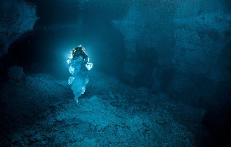 """A DAMA DA CAVERNA   A Caverna Ordinskaya (ou """"Caverna Orda""""), que fica sob os Montes Urais, na Rússia, é a maior caverna de cristal de gesso do mundo e uma das mais longas cavernas subaquáticas, com muitas áreas ainda inexploradas. Uma lenda conta que um espírito conhecido como A Dama da Caverna vigia todos os que entram em suas águas. O fotógrafo Victor Lyagushkin usou a ajuda de Natalia Avseenko, campeã mergulho, para recriar o mito nas águas geladas da caverna. Clique na foto para saber…"""