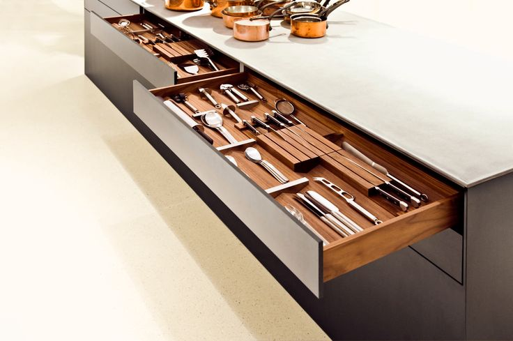 This photo shows the interior fitting system done in a walnut finish. The modular knife blocks come in two sizes and can be positioned in the drawers according to one's needs. The photo also shows the sliding dividers in stainless steel. www.bulthaup.com #bulthaup #kitchens