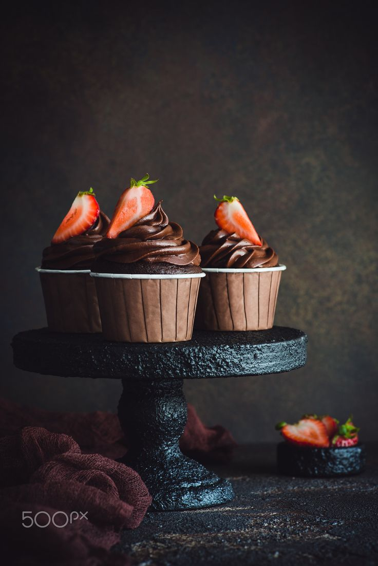 Chocolate cupcakes with cheese frosting - Chocolate cupcakes with cream cheese frosting and fresh strawberry on cakestand over dark bachground, selective focus, vintage look