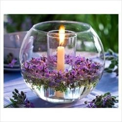 candle in a glass within a glass bowl with floating flowers