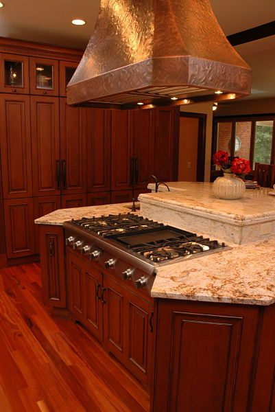 Kitchen island with cooktop and hood by Neal's Design Remodel.