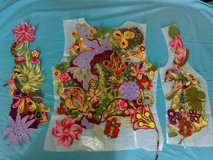 Piecing together freeform crochet motifs onto pattern.