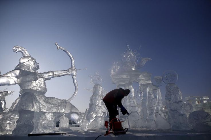 A worker polishes an ice sculpture ahead of the Harbin International Ice and…