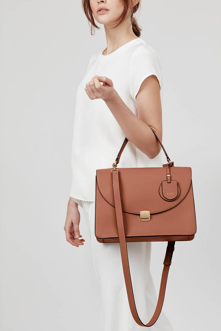 Feminine meets functional. Our structured top-handle bag delivers a polished sensibility for every season. Designed in San Francisco and crafted in Italy, this bag reveals thoughtful pockets including one back exterior slip pocket for easy organization. Its custom gold hardware is showcased in the form of a signature front lock closure. Just add the detachable crossbody strap for an added level of ease, and a matching monogram charm for a personalized touch.