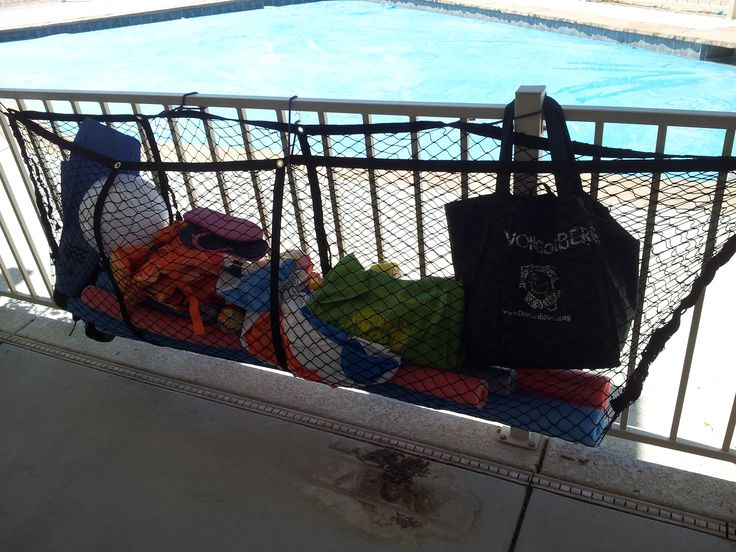 My version of the cargo net pool toy storage! $20 for the net from the auto dept in that big store. Some bungee cords (purple!) and I laced up the sides with heavy cord,. Brutal sun here so this hangs in the shady area but still accessible to the pool.