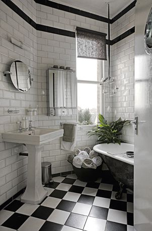 Black and white bathroom with pedestal sink, claw foot tub, and floor-to-ceiling tile