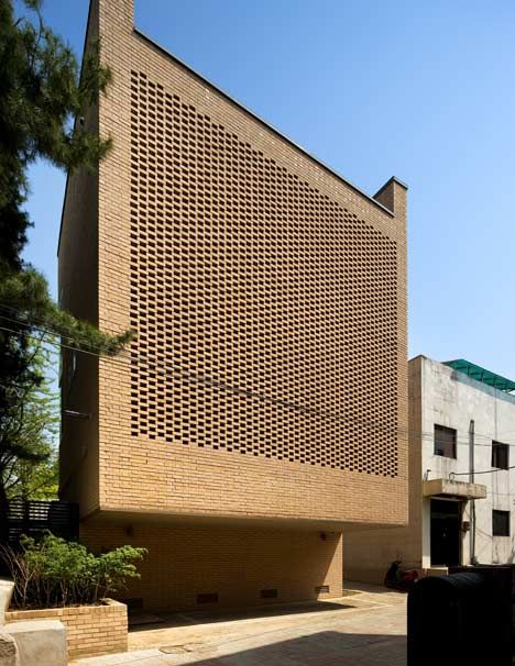 A towering wall of perforated brickwork lets light filter gently into the rooms of this house