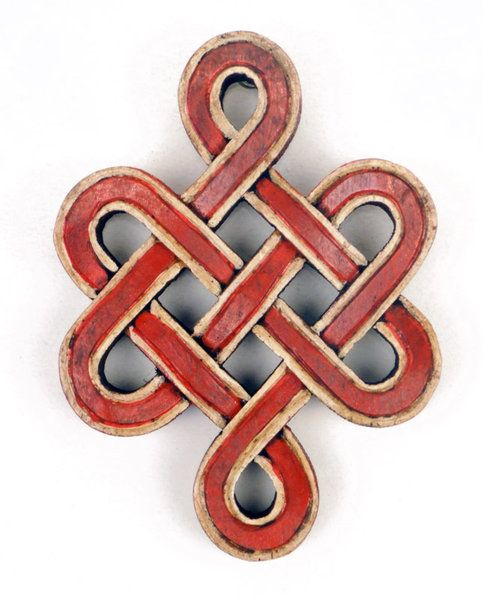 The Buddhist endless knot is a closed, graphic ornament composed of right-angled, intertwined lines. It overlaps without a beginning or an end, symbolizing the Buddha's endless wisdom and compassion. It indicates continuity as the underlying reality of existence. It is conjectured that it may have evolved from an ancient naga symbol with two stylized snakes.