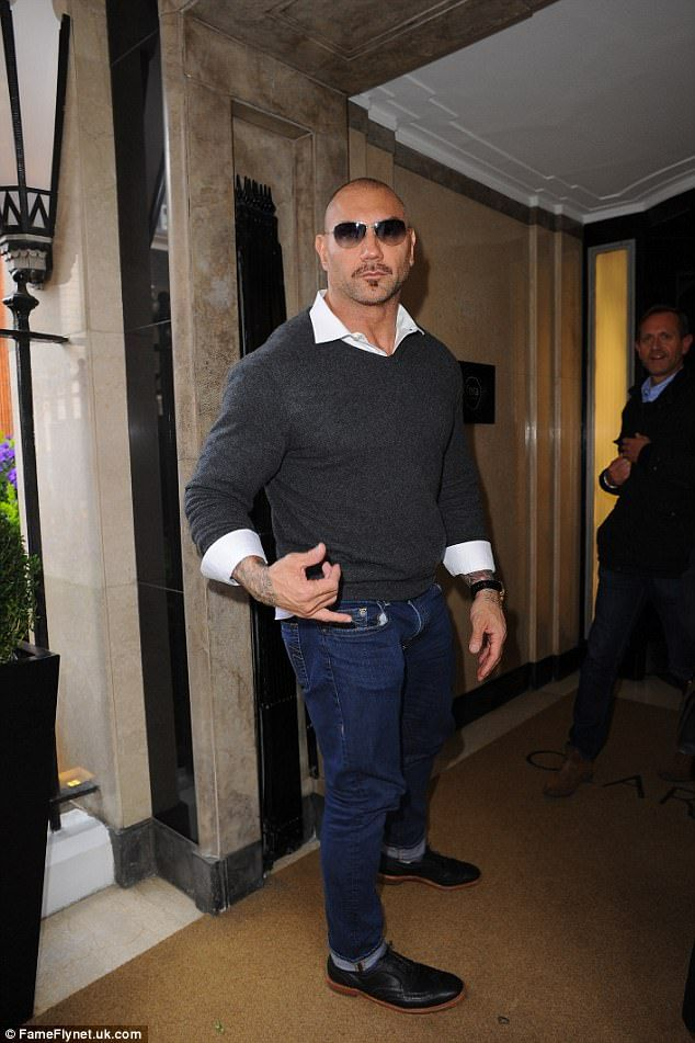 Dashing! Dave Bautista, 48, opted for a casual ensemble with a pair of blue jeans and a sl...