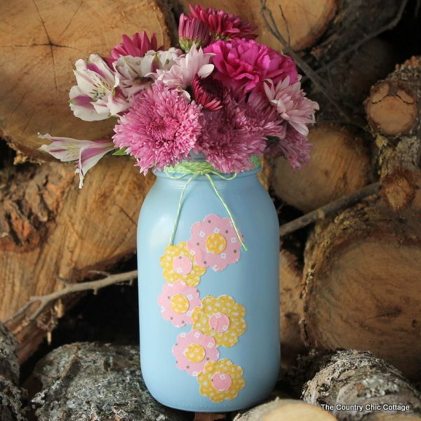 A fun mason jar spring vase with fabric flowers on the front. This is super simple to make and includes a video tutorial on how to make your own.