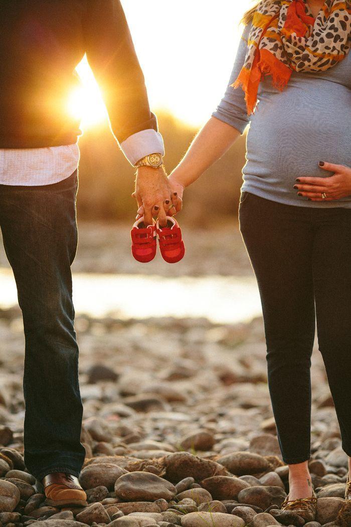 Sesión de fotos de maternidad papás sosteniendo los zapatos del bebé