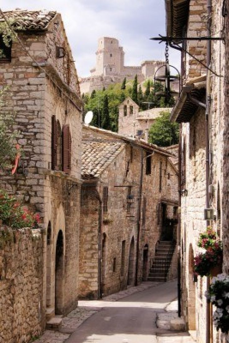 Medieval street in the Italian hill town of Assisi with castle in the background