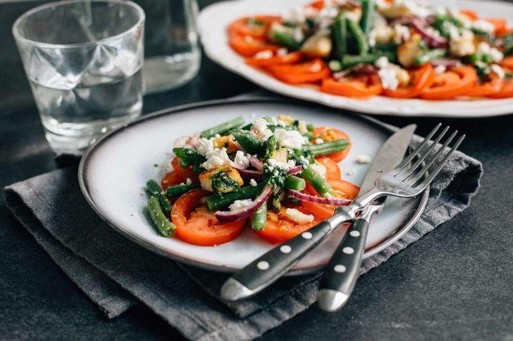 Recept voor sperziebonen-tomaten salade voor 4 personen. Met zout, boter, water, olijfolie, peper, sperzieboon, trostomaat, wit brood, feta, rode ui, basilicum, peterselie, witte wijnazijn en knoflook