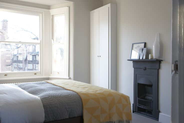 Grey, Black, Yellow, White. farrow and Ball - Ammonite, Simple bedroom design. Reclaimed fireplace.