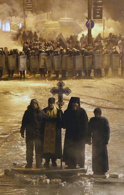 Ukraine, February 2014. Orthodox priests standing between Ukrainian protesters and Ukrainian police forces, praying for peace.