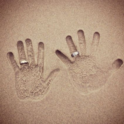 hand prints in the sand with wedding rings