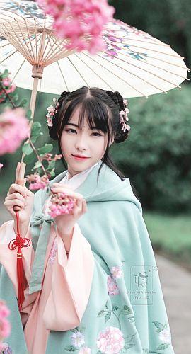 eggpuffs:  衔泥小筑 汉服女装 锦绣年华二 重工刺绣超大摆斗篷 国色 豆绿   Hanfu (han chinese clothing) from 衔泥小筑. She wears a   green Doupeng/斗篷 (cape/cloak) over a pink Ming Dynasty-style Aoqun/袄裙.