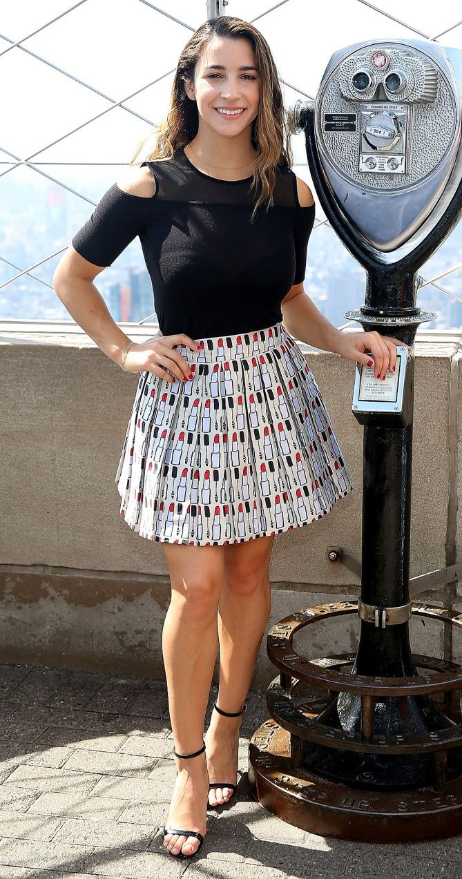 Aly Raisman in a black cold shoulder top and lipstick-print skirt