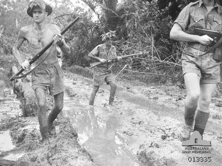 Australian troops plough through the mud at Milne Bay, New Guinea, shortly after the unsuccessful Japanese invasion attempt.