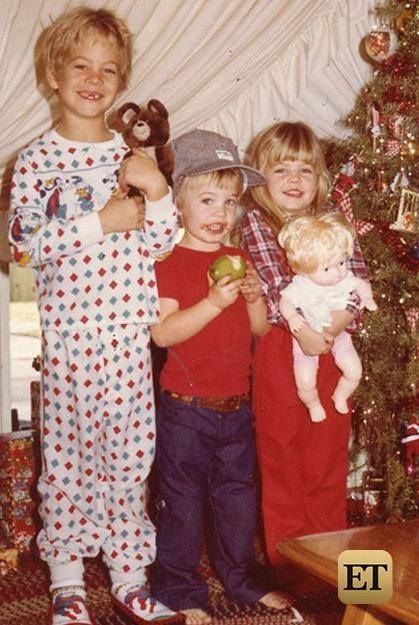 """Paul wearing """"Spider Man"""" house slippers, and flannel pajamas holding a stuffed bear at Christmas 1980."""