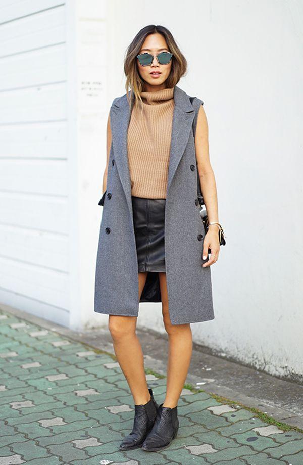 Aimee Song usa turtleneck top caramelo com mini saia de couro preta, maxi colete cinza e botas de cowboy preta