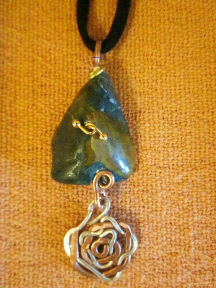 This is a green/yellow chalcedony pendant with copper/silver spiral, copper hook and some brass on. It is a powerful cleanser, including open sores. Mothers use it to increase lactation, and it also fosters the maternal instinct. It increases physical energy. Healers use it to decrease ill effects of senility and dementia as well as to heal the eyes, gallbladder, bones, spleen, blood and circulatory system.