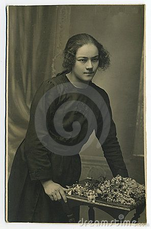 This original antique photo is taken in the North of italy. A young woman with flowers.