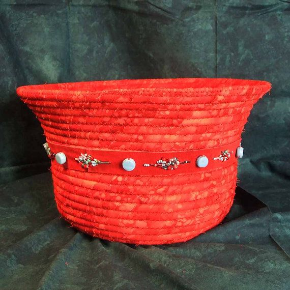 Red batik cotton fabric was coiled around 10/32 fibrecoil and zigzagged into a basket . Cinched with a red suede strap embellished with glass beads and a metal concho, this a fitting addition to southwestern style decor. Large and sturdy, but light in weight, rim is 12 inches in diameter, base is 8 inches and height is 7 inches. I have more photos if you would like to see them.  Mails parcel post with insurance. Postal over charges are refunded to the nearest dollar.