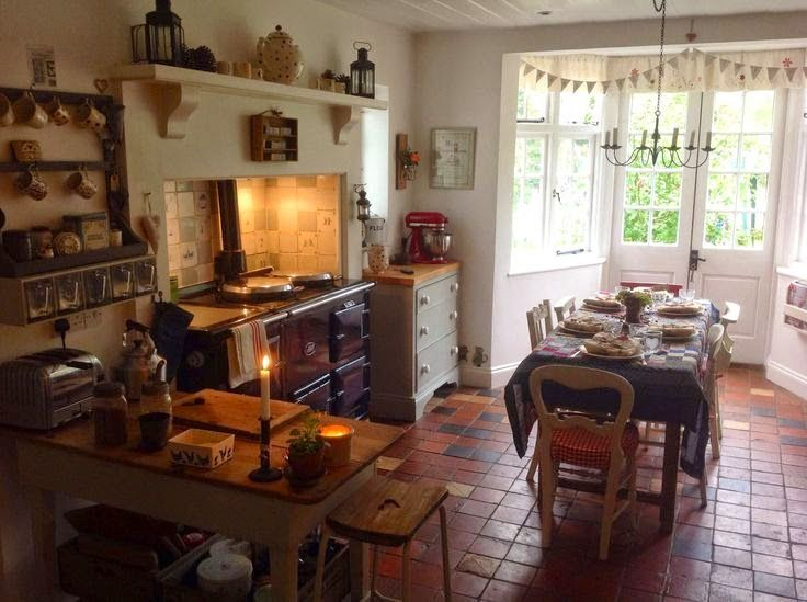 Gorgeous country kitchen with an Aga and tiled floor.