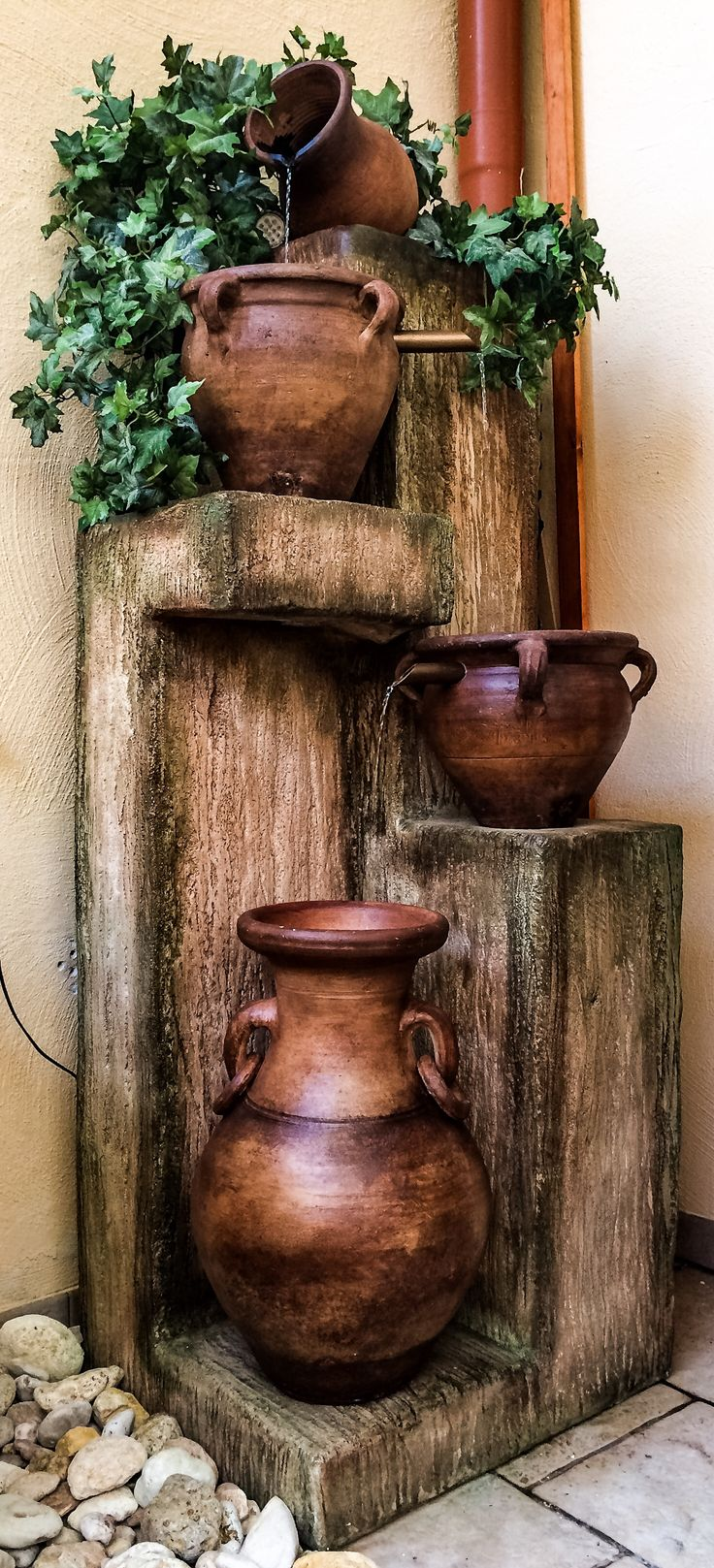 Old pottery transformed into a beautiful backyard fountain. The structure is made from concrete.