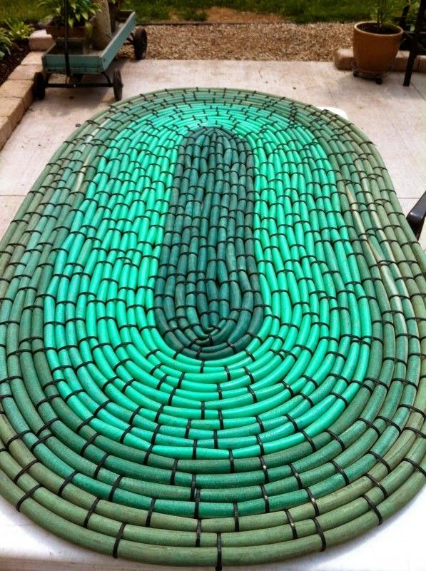 I used old garden hoses and black zip ties to create a large oval rug to use in front of my planter's bench.