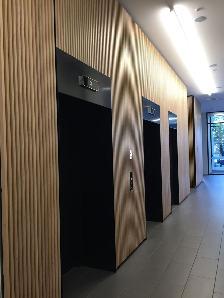 Photo 2: timber cladding in this lift area looks lovely and modern and protects/ conceals dings and marks on the walls