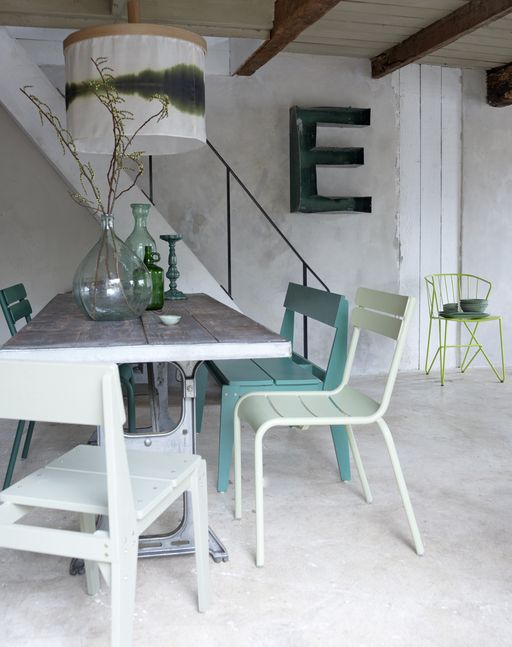 minimalist dining room. concrete floor. concrete walls. white and blue turquoise chairs. handblown glass vase. large letter wall art. exposed beams. plank ceiling. reclaimed wood + metal table.