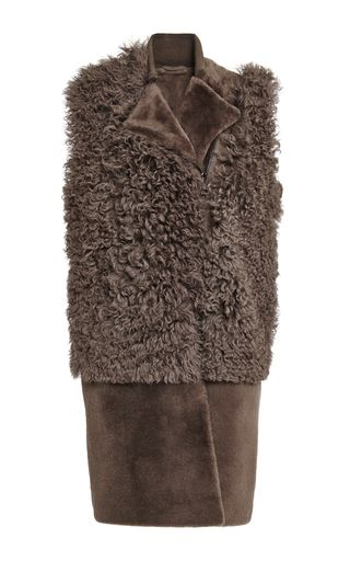 This vest by **Rizal** is rendered in taupe shearling and features smooth notched lapels opposing the more textured body.