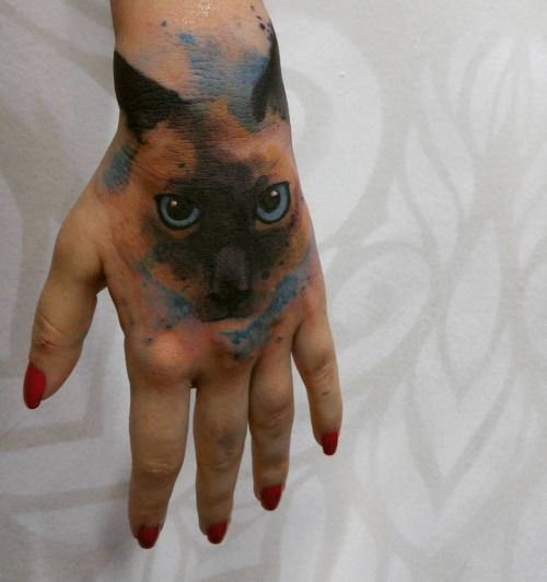 Tatuaje de estilo acuarela de la cara de un gato situado en la...