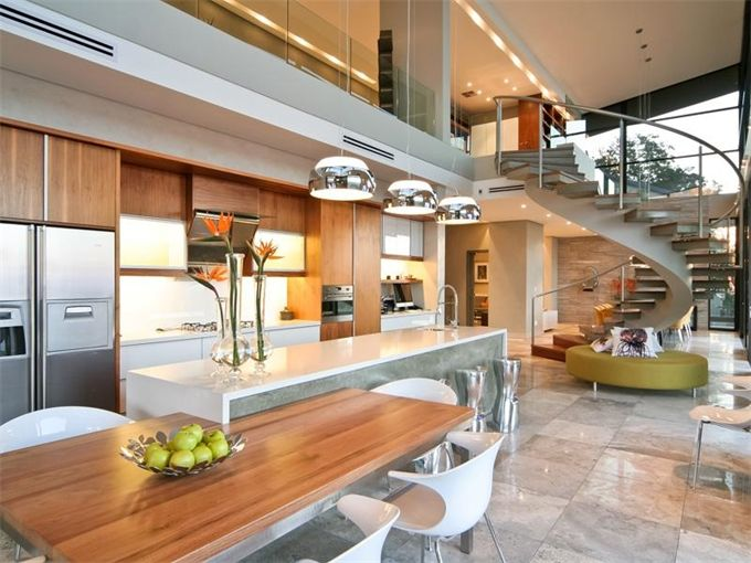 The curved staircase is echoed in the pendant light fixtures and modern chairs.