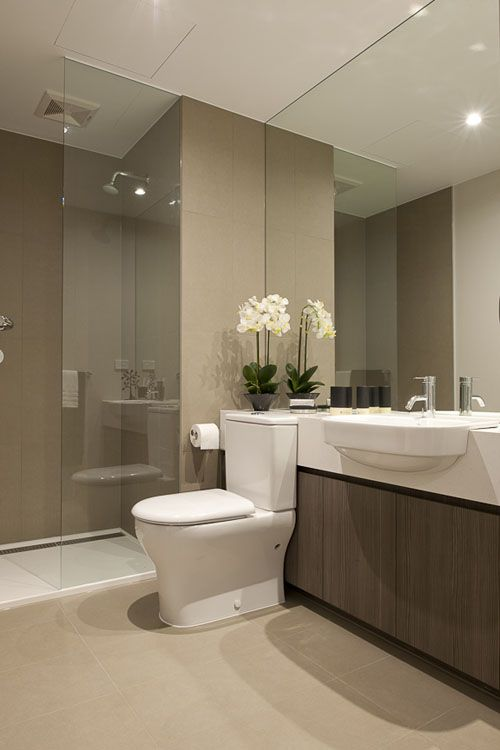 Beautiful modern bathroom, neutral, interesting countertop / toilet idea.