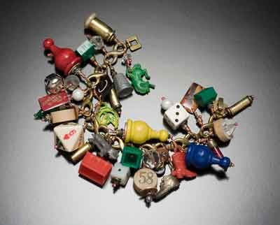 Game pieces, a bracelet by Robin Ayres; game pieces are a symbol of recreation, and often also of gambling and chance.