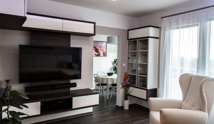 Ve stejné výšce na televizní stěnu navazuje prosklená skříňka, umístěná do rohu místnosti