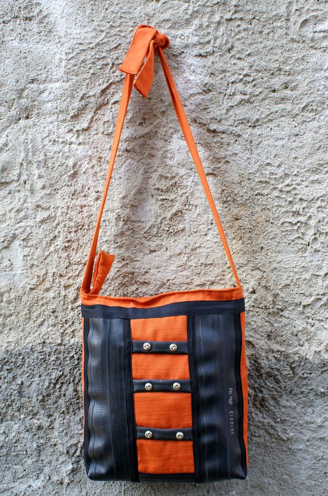 Shoulder bag with adjustable strap with knot, handmade with orange cotton fabric, decorated with recycled bike tubes, black cotton ribbon and buttons with chrome effect. Secure zip closure. Inside lining of white cotton, an interior zippered pocket, an interior opened pocket for cell phone. It's a sporty bag, perfect for everyday wear.