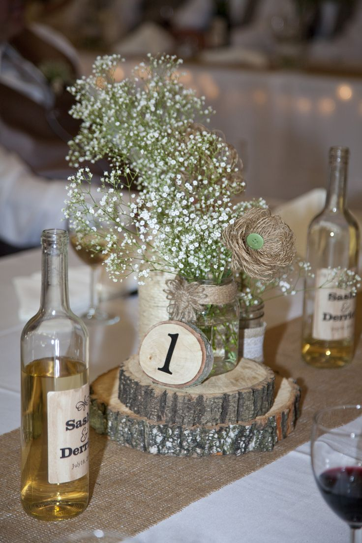 Rustic center pieces with babies breath flowers ordered in bulk from Costco. Wood Slabs and decorated mason jars.