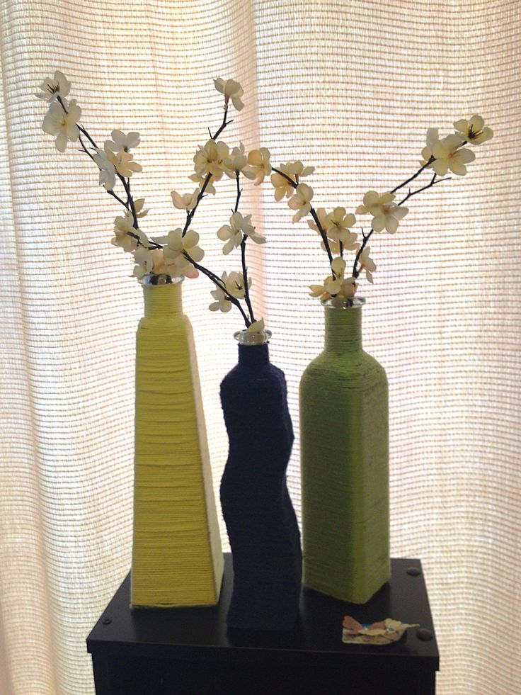 Different shaped bottles covered with different yarn colors. This would be cool for the top of our cabinets.