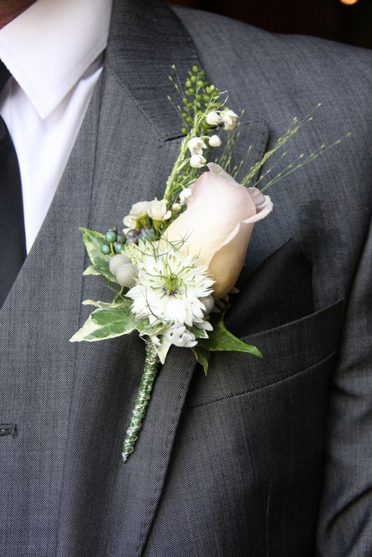 The Groom's Boutonniere in silver grey shades; a Metalina Rose with Lily of the Valley, Viburnum Pewter berries, Thalaspi, Champagne Grass, Silver Brunia and Love in the Mist