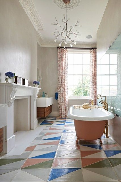 The statement bath is painted in a bespoke salmon pink to match the coloured terracotta floor tiles in pink, soft grey, white, khaki and petrol blue.