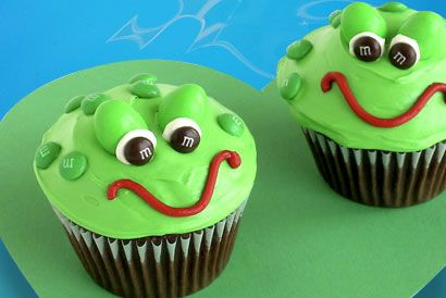 Frog Cupcakes - 1 box (18.25 oz.) chocolate cake mix 1 ½ cans (16 oz. each) vanilla frosting 1 tube (6 oz.) red decorating icing Green food coloring ⅓ cup M&M'S® Brand MINIS® Milk Chocolate Candies 48 pieces M&M'S® Brand Peanut Chocolate Candies 2 (12-cup) cupcake pans Spatula 24 paper cupcake liners Resealable plastic bag