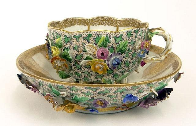 19th Century Meissen Porcelain Gilt Decorated Cup and Saucer with Applied Flowers. Signed Crossed Swords. Usual Losses to Flowers or else Good to Very Good Condition. Saucer Measures 5-1/8 Inches Diameter. Shipping $40.00