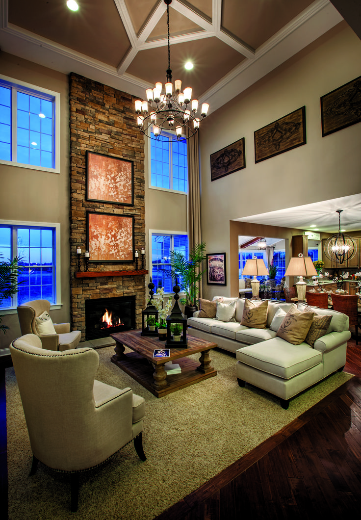 This open living room is filled with texture including wood floors, a large carpet rug, and a stone fire place. (Toll Brothers at Monroe Chase, NJ)